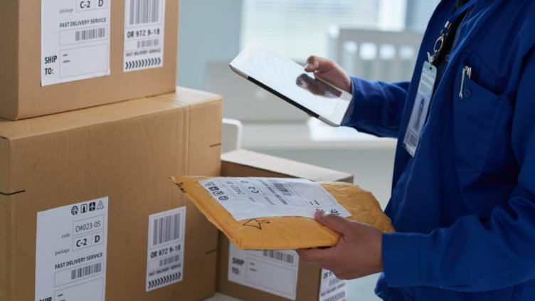 Close-up image of mail worker checking information on parcels; Shutterstock ID 584392576; Departmental Cost Code : 162800; Project Code: GBLMKT; PO Number: GBLMKT; Other: